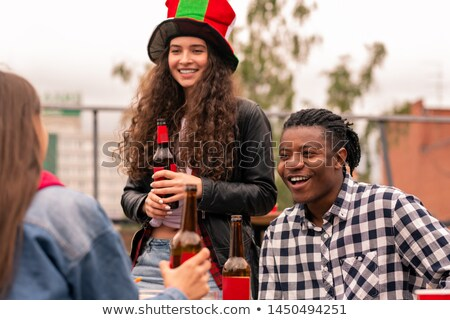 Young intercultural couple of soccer fans having beer while chatting with friend Stock photo © pressmaster