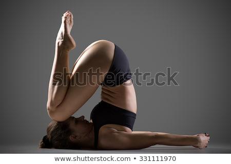 Woman in variation of plough Yoga posture (Halasana) Stock photo © lichtmeister