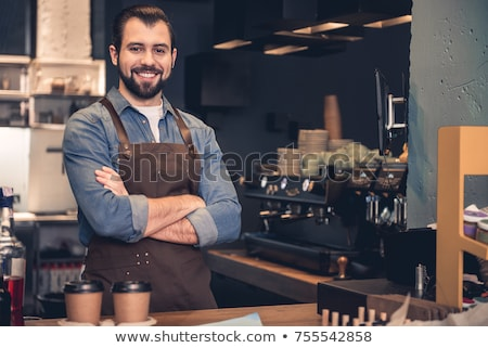 young male barista in uniform standing by table with working equipment stock photo © pressmaster