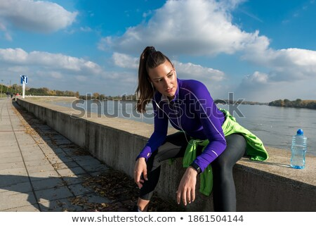 young sporty woman with earphones taking break after a run in th stock photo © boggy