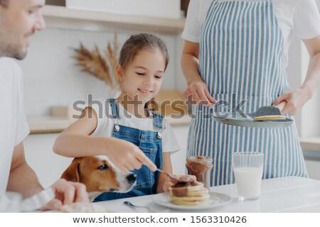 Glad small girl enjoys eating tasty dessert prepared by mum, adds melted chocolate to pancakes, enjo Stock photo © vkstudio