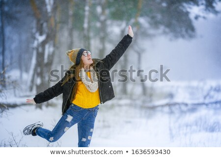 A woman in the winter period has fun and enjoys life in the snowy outdoors Stock photo © ElenaBatkova