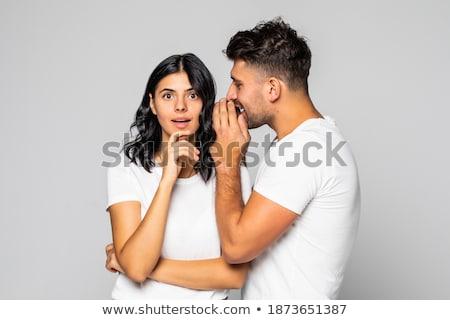 happy couple whispering over grey background Stock photo © dolgachov