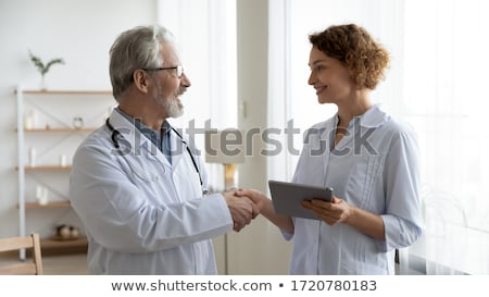 Two People In Comunication - Handshaking with Tablet Computers,  Stock photo © adamr
