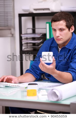 Tradesman looking a light switch up on the computer Stock photo © photography33