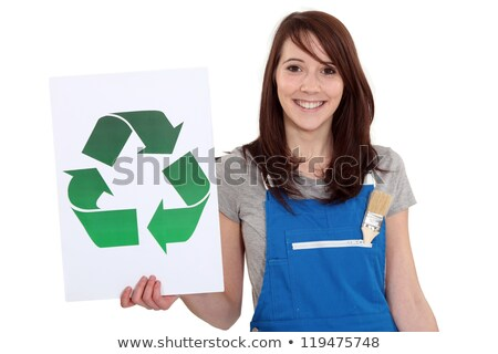 Stock photo: A female manual worker holding a recycle sign.