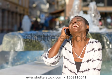 young woman laughing as she chats on her mobile stock photo © dash