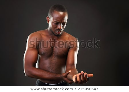 African man checking pulse over black background Stock photo © deandrobot