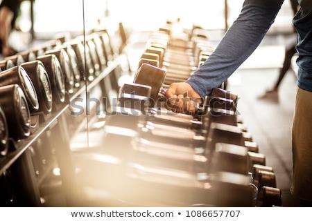 привлекательный молодым человеком тяжелая атлетика гантели Сток-фото © stokkete