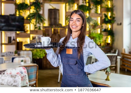 Long-haired beautiful woman in apron holds a tray with food in h Stock photo © Yatsenko