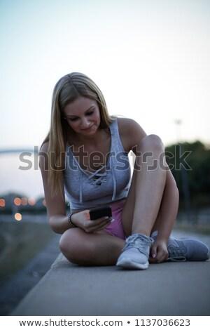 молодые спортивный женщину смартфон вечер Сток-фото © chesterf