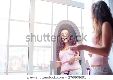 woman looking at weight loss in mirror Stock photo © IS2
