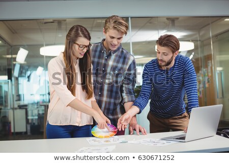 Graphic designers interacting with each other while working at desk Stock photo © wavebreak_media