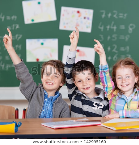 Schoolchildren raise their hand in a primary class Stock photo © monkey_business