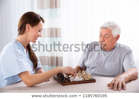 Caretaker Playing Chess With Senior Man On Desk Stock photo © AndreyPopov