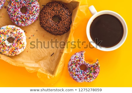 Delicious glazed donuts and cup of coffee on yellow surface Stock photo © artsvitlyna