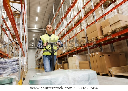 warehouse worker carrying loader with goods Stock photo © dolgachov