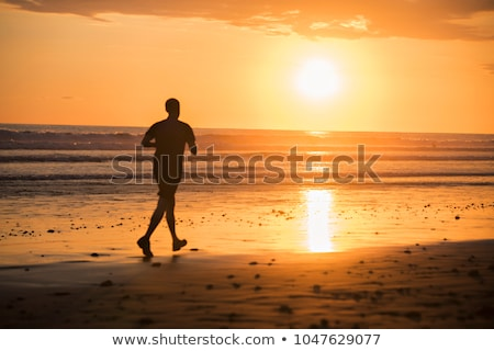 Jogger on a beach at sunset silouhaite Stock photo © Lopolo