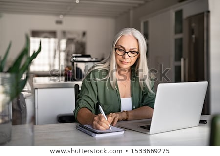 Starszy kobieta piśmie notebooka dziennik domu Zdjęcia stock © dolgachov