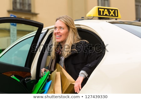 Women with shopping bags getting out of taxi Stok fotoğraf © Kzenon