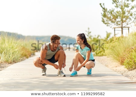 Stock photo: couple of joggers tying sneakers shoelaces