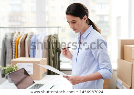 Pretty young manager of online shop reading paper with list of goods Stock photo © pressmaster