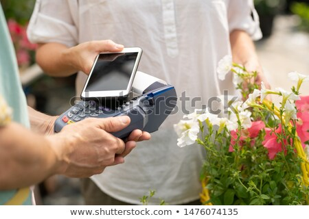 Young client of flower shop holding smartphone over payment machine Stock photo © pressmaster