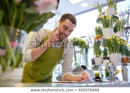 Virágárus férfi vágólap virágüzlet pult vásár Stock fotó © dolgachov