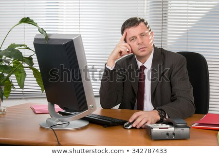 Serious businessman at desk. Stock photo © lichtmeister