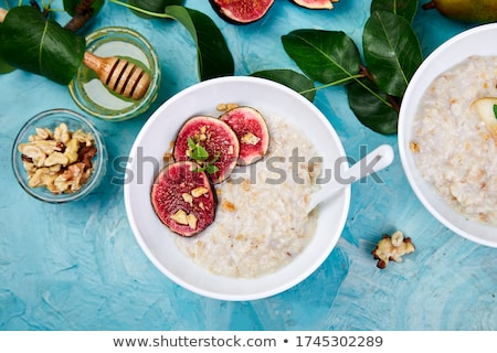 A bowl of porridge with figs slices and walnuts. Stock photo © Illia