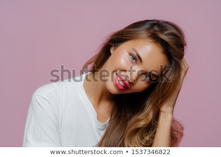 Portrait of good looking pleased female model tilts head, has toothy smile shows white perfect teeth Stock photo © vkstudio