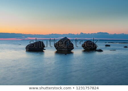 Stock photo: View of a rocky coast at sunset time. Long exposure vertical sho