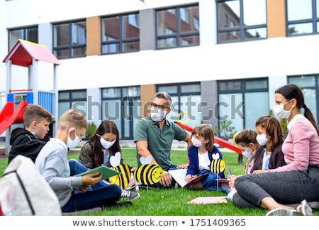 Woman with face mask sitting outside as lockdown opens Stock photo © Kzenon