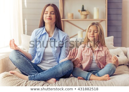 Little girl meditating in lotus pose with closed eyes Stock photo © Illia