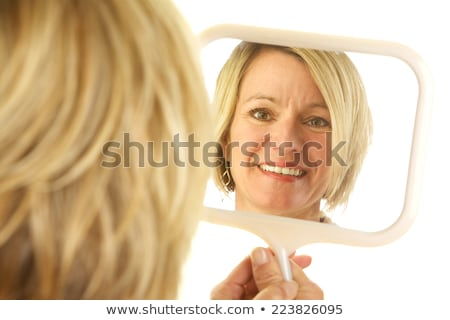 Studio shot of a woman looking at her reflection in a mirror Stock photo © photography33