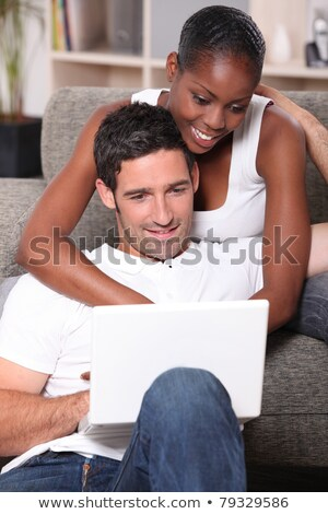 black woman is cuddling her boyfriend and doing computer Stock photo © photography33