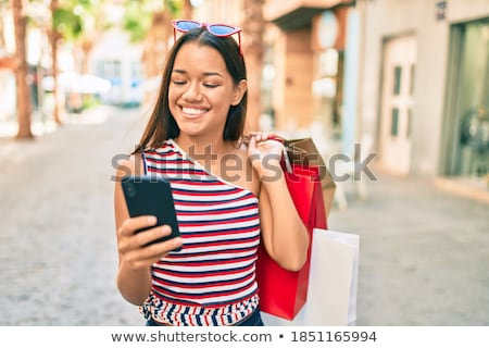 Cool young shopper using smartphone. Stock photo © lithian