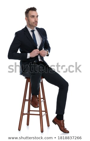 business man sitting on a stool while fixing his jacket stock photo © feedough