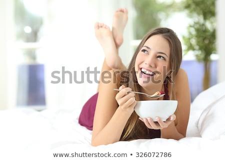 улыбающаяся женщина еды злаки молоко кровать спальня Сток-фото © deandrobot