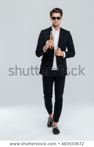 Handsome pensive man standing over gray background Stock photo © deandrobot