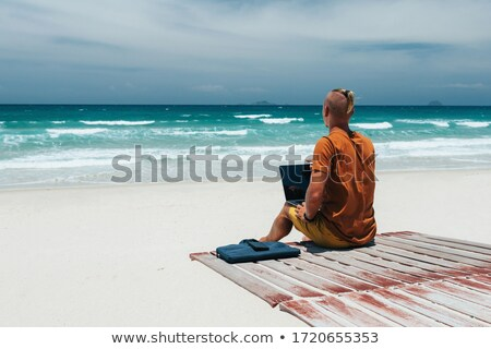 Male on a beach using his computer Stock photo © IS2