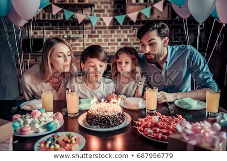 Boy with dad blowing out candles on cake Stock photo © IS2