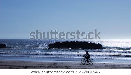 Man riding bicycle in wet sand on beach Stock photo © IS2