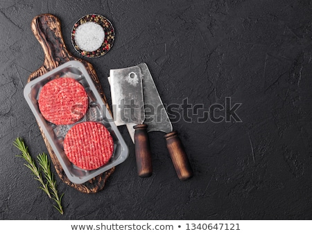 Plastic tray with raw minced homemade meat beef burgers with spices and herbs. Top view and space fo Stock photo © DenisMArt