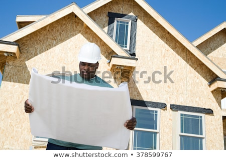 Owner and Worker on construction site reading blueprint plan Stock photo © Kzenon