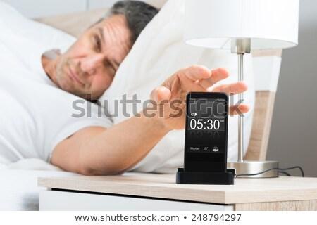 Man Snoozing Alarm On Mobile Phone Stock photo © AndreyPopov