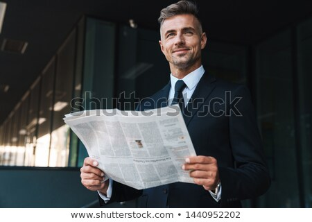 Photo of bearded man in businesslike suit reading newspaper on b Stock photo © deandrobot