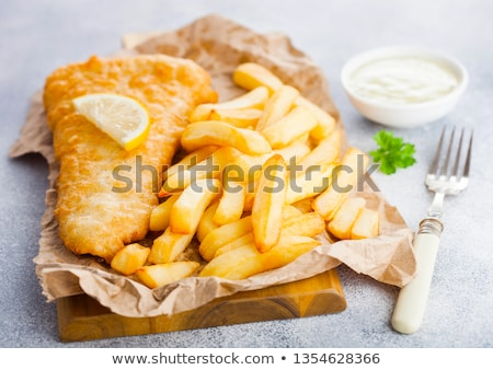 traditional british fish and chips with tartar sauce on chopping board and lemon slice on white ston stock photo © denismart