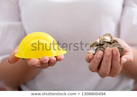 Személy tart munkavédelmi sisak arany érmék közelkép Stock fotó © AndreyPopov