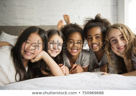 large group of her friends taking goog time on bed Stock photo © Lopolo